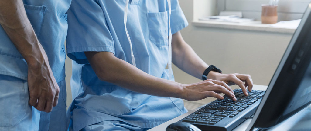 two doctors typing on a computer